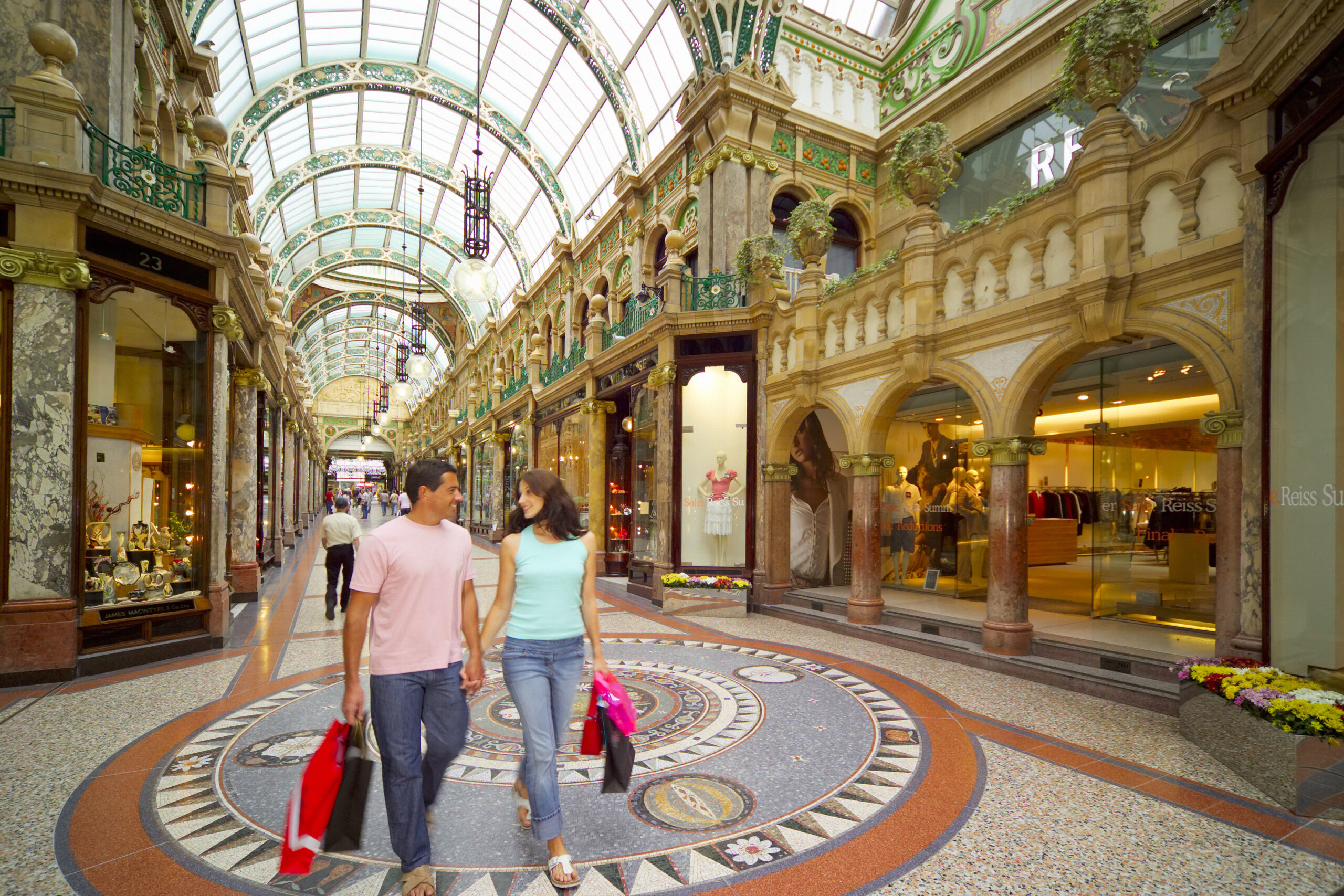 A couple walk whilst holding shopping bags through the 19th c. County Arcade, one of two arcades making up the Victoria Quarter in Leeds